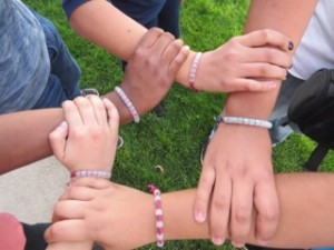 Students holding hands showing unity, respect, and equality.