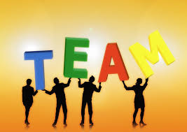 An image of individual people holding a single letter to spell out the word team.