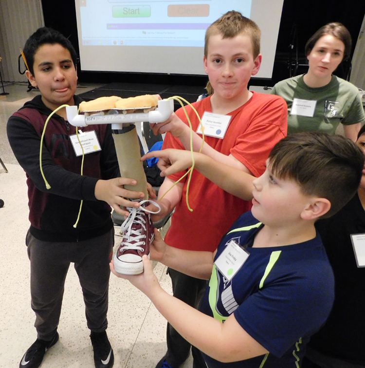 Middle school SMILE club students building a prosthetic leg.