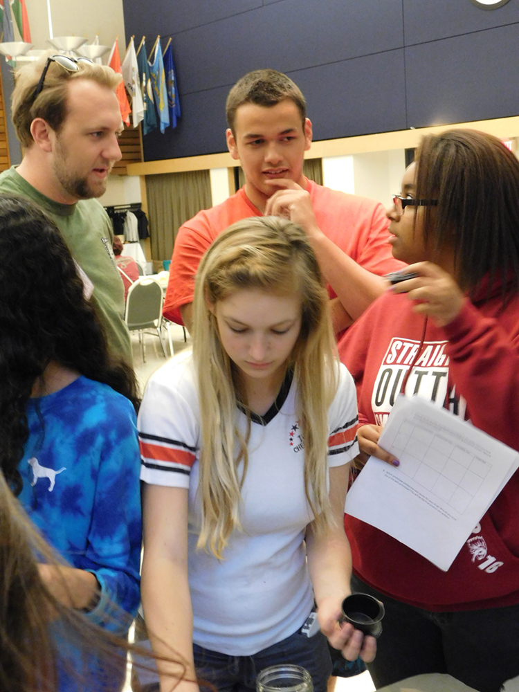 OSU student mentor works with students at the high school challenge