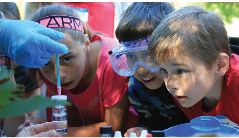Students observing water sample test at outdoor camp
