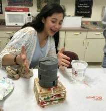 Student placing weight on gingerbread house